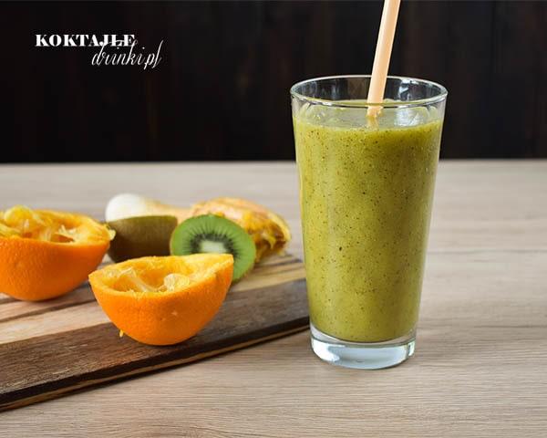 Koktajl owocowy smoothie o zielonej barwie, w otoczeniu wyciśniętej pomarańczy i kiwi.