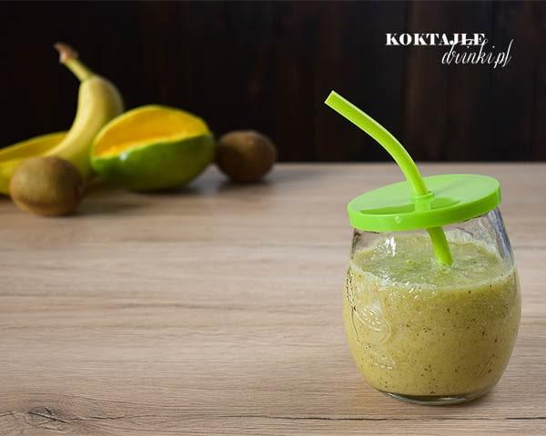 Koktajl owocowy smoothie o barwie zielonej, w tle widoczne banany, kiwi oraz mango.