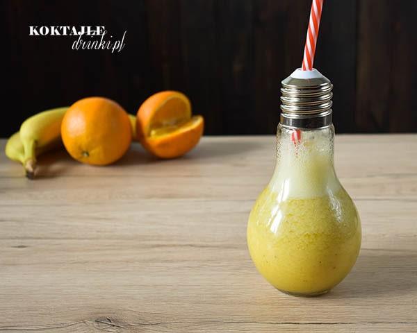 Koktajl smoothie owocowe o barwie ciemno żółtej w szklance żarówce, na drugim planie pomarańcza oraz banan.