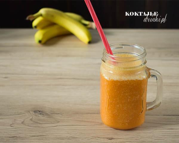 Koktajl smoothie owocowy o barwie pomarańczowej w szklance, na drugim planie banany.