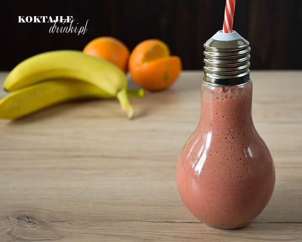 Koktajl owocowy smoothie o barwie jasno czerwonej, w otoczeniu bananów i pomarańczy.