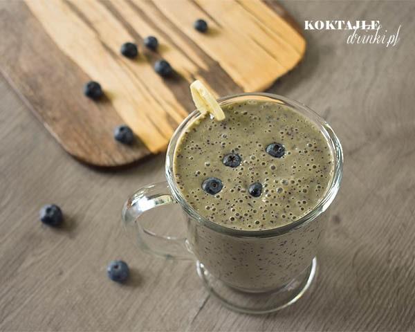 Koktajl warzywny smoothie o barwie jasno brązowej w otoczeniu borówek i z plastrem banana.