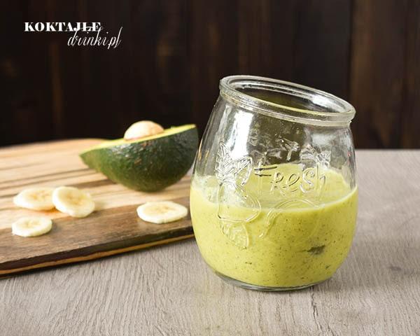 Koktajl owocowo-warzywny smoothie o jasno zielonej barwie, na drugim planie widoczne awokado i plastry banana.