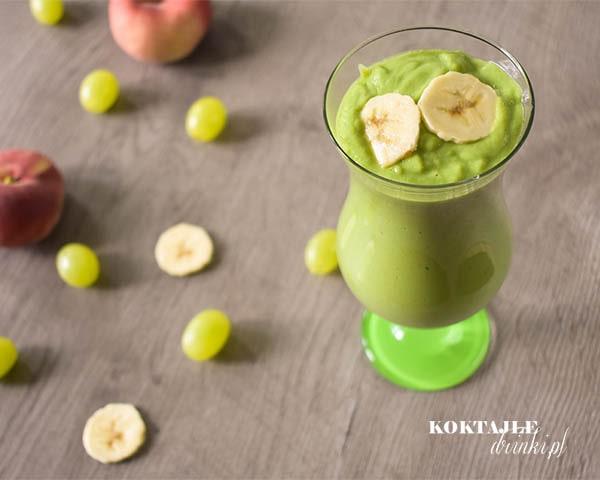 Koktajl warzywny smoothie o barwie jasno zielonej, w tle winogrona, plastry banana i brzoskwinie.