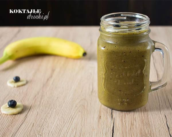 Koktajl warzywny smoothie o barwie jasno brązowej, w tle widoczne borówki i banan.