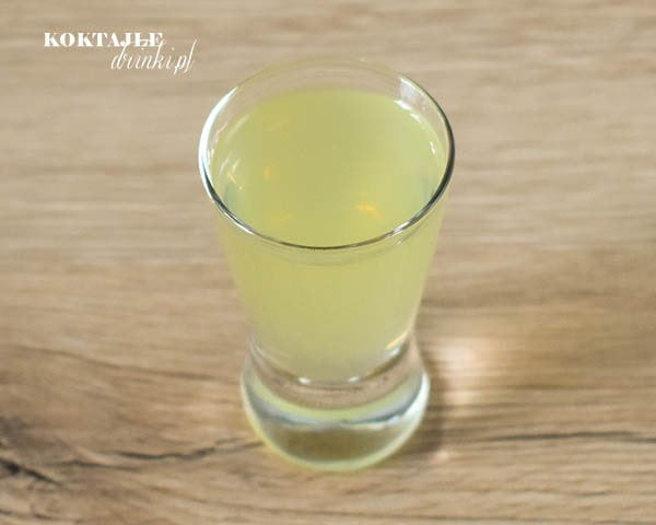 Widok z góry na shot cytryna i wódka o jasno żółtej barwie.